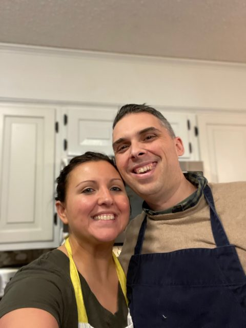 A photo of Heidi and Jason Clarke wearing aprons in the kitchen.
