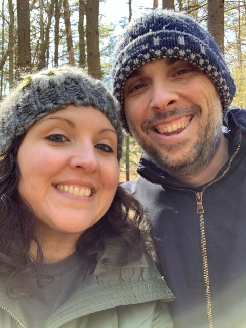 Heidi Clarke and Jason Clarke dressed in hats and coats on a walk in the woods